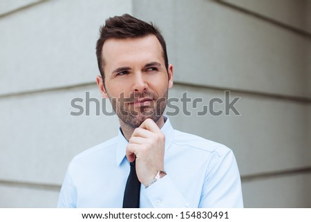 Thoughtful businessman standing outside the office