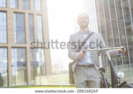 Thoughtful businessman standing with bicycle outside building - stock photo