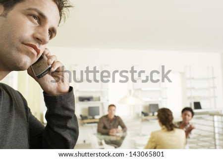 Thoughtful businessman using mobile phone with colleagues discussing in background - stock photo