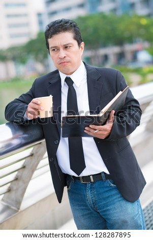 Thoughtful businessman with coffee and notebook in hands