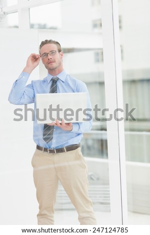 Thoughtful businessman with glasses holding laptop in the office