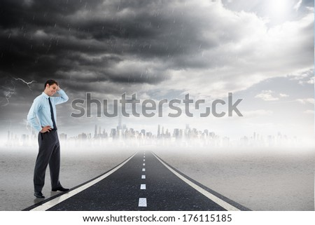 Thoughtful businessman with hand on head against open road background
