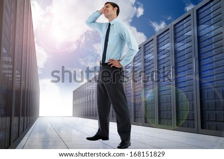 Thoughtful businessman with hand on head against server hallway in the sky - stock photo