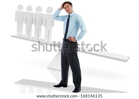 Thoughtful businessman with hand on head against white scales with human figures
