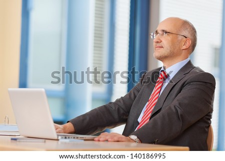 Thoughtful businessman with laptop looking up at office desk - stock photo