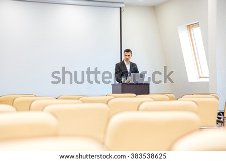 Thoughtful businessman writing speech on laptop in empty conference hall - stock photo