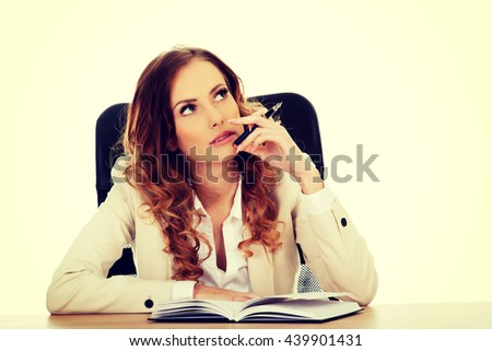 Thoughtful businesswoman by a desk - stock photo