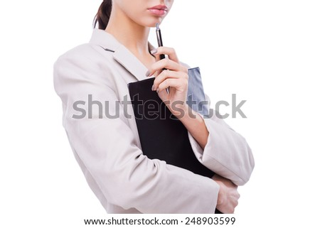 Thoughtful businesswoman. Close-up of confident young businesswoman holding clipboard and pen on chin while standing against white background - stock photo