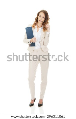 Thoughtful businesswoman holding a clipboard.