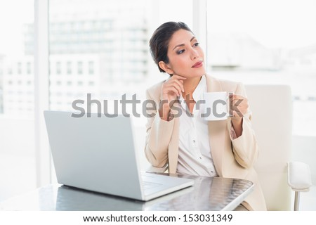 Thoughtful businesswoman holding mug while working on laptop in her office