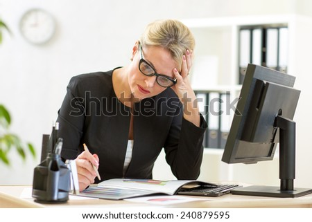 thoughtful businesswoman looking at business papers in office - stock photo