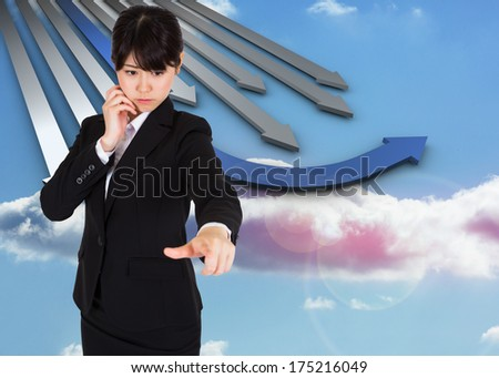 Thoughtful businesswoman pointing against blue and grey curved arrows pointing against sky