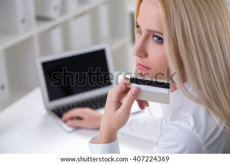 Thoughtful businesswoman sitting at desk in office and holding credit card