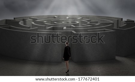 Thoughtful businesswoman standing near the enter of labyrinth