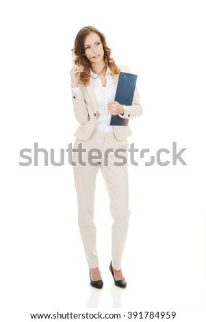Thoughtful businesswoman with clipboard.