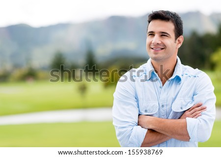 Thoughtful casual man outdoors looking up and smiling  - stock photo