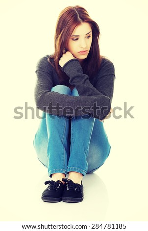 Thoughtful casual woman sitting on the floor. - stock photo
