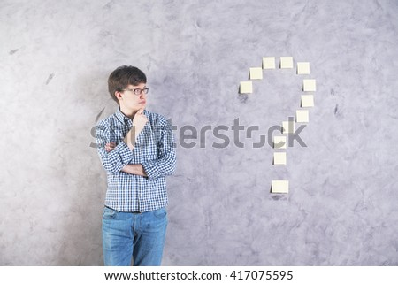 Thoughtful caucasian businessman standing against grey concrete wall with sticker question mark  - stock photo