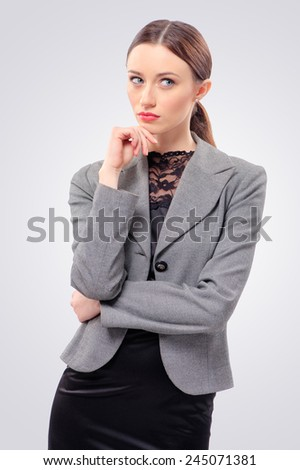Thoughtful caucasian businesswoman looking away and touching her face, isolated on grey - stock photo