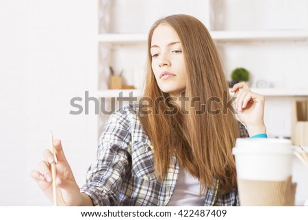 Thoughtful caucasian female sitting in office and looking at pencil in hand - stock photo