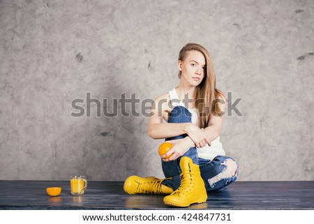 Thoughtful caucasian woman in yellow boots sitting next to orange juice and fruit on concrete wall background - stock photo