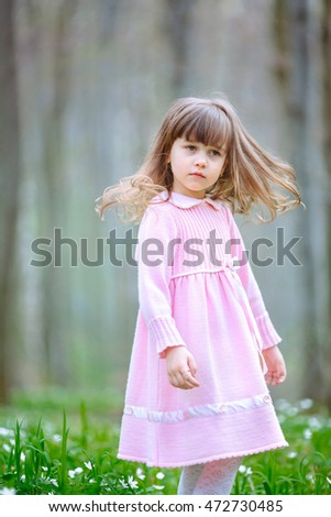 Thoughtful child in pink dress shakes her hair while standing on the glade