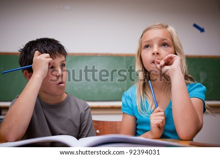 Thoughtful children working together in a classroom - stock photo