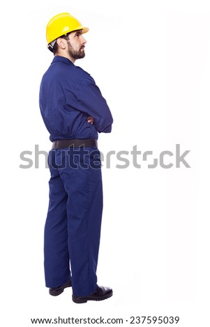 Thoughtful contractor standing with arms crossed on white background