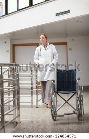 Thoughtful doctor standing next to a wheelchair in hospital hallway - stock photo