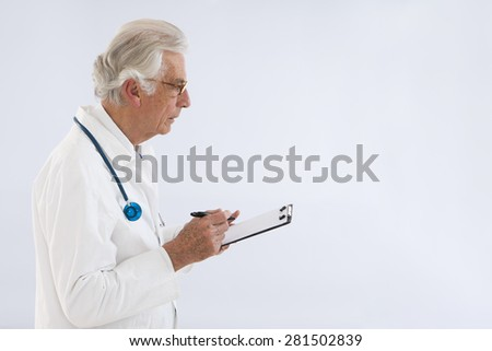 thoughtful doctor witting on clipboard - stock photo