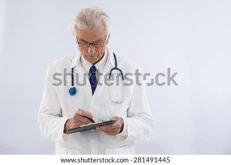 thoughtful doctor writing on clipboard - stock photo