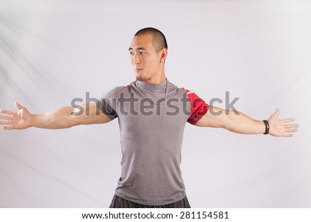 Thoughtful East Asian man in grey shirt, stretching before exercising