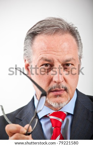 Thoughtful elder businessman holding a pair of glasses