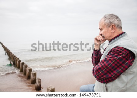 Thoughtful elderly man standing on the beach on a foggy day