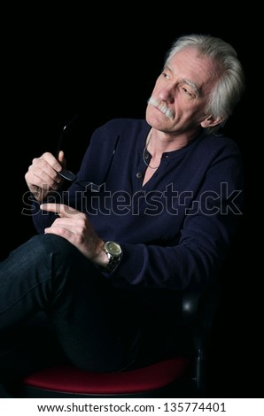 Thoughtful elderly man with Eyeglasses in hands - stock photo