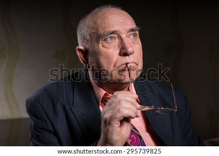 Thoughtful elderly man with his glasses in his hand staring up into the air with a sombre expression as her reminisces on his past life - stock photo