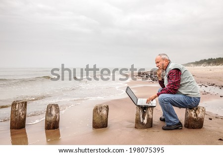 Thoughtful elderly man with the laptop sits on a sea background