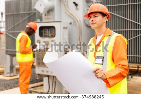 thoughtful electrical engineer in electric substation - stock photo