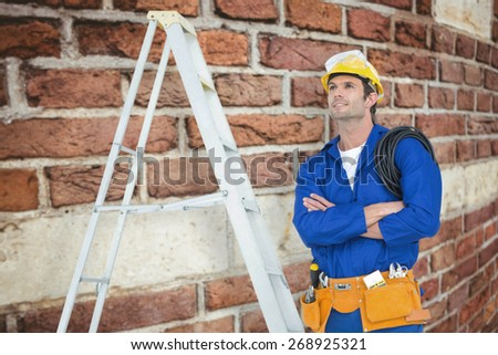Thoughtful electrician with arms crossed by ladder against red brick wall - stock photo