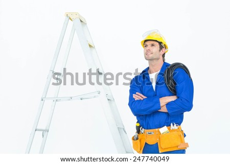 Thoughtful electrician with arms crossed standing by ladder over white background - stock photo