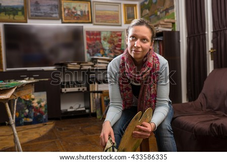 Thoughtful female painter sitting painting in a studio or gallery holding a colorful artists palette and paintbrush in her hand - stock photo