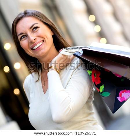 Thoughtful female shopper carrying shopping bags - stock photo