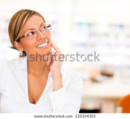 Thoughtful female student at the library looking up - stock photo