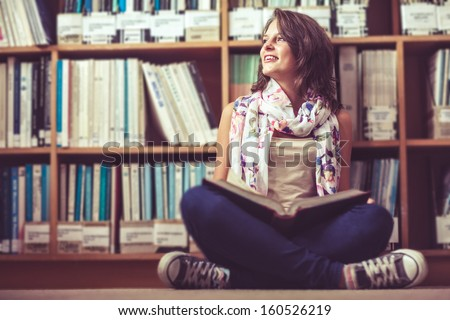 Thoughtful female student sitting against bookshelf with a book on the library floor - stock photo