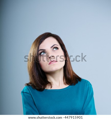 thoughtful girl in a blue t-shirt looking up on a gray background