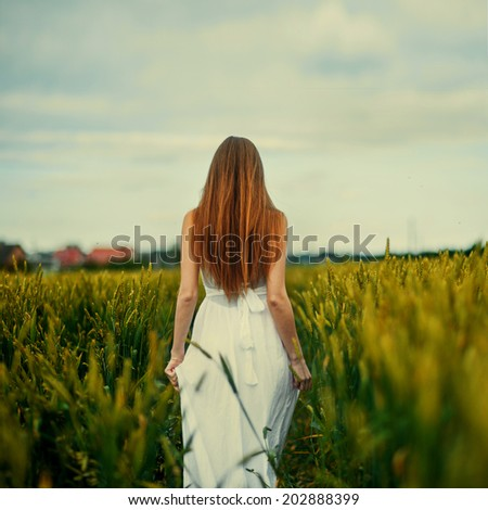 thoughtful girl in a dress in the back standing - stock photo