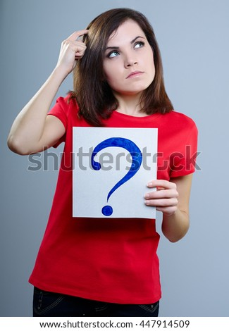 thoughtful girl in a red T-shirt on a gray background holding a question mark