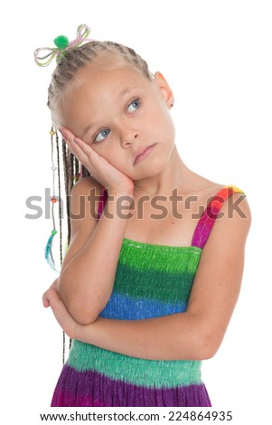 Thoughtful girl in a summer dress. The girl is six years old. - stock photo