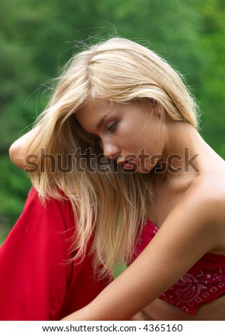 thoughtful girl in red clothes sitting outdoor