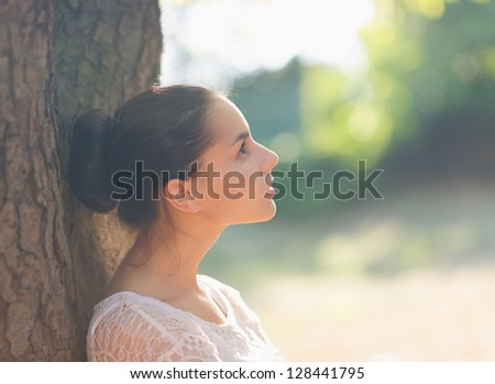 Thoughtful girl leaning on tree and looking on copy space - stock photo